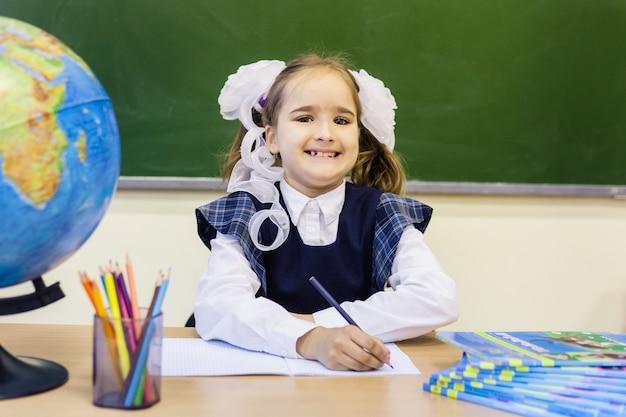 Meisjesschoolmeisje en school. het meisje draagt een schooluniform op school. opleiding
