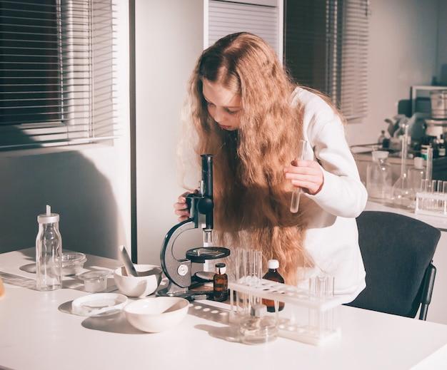 Meisjesschoolmeisje gebruikt een microscoop in het schoollaboratorium. kinderen en onderwijs