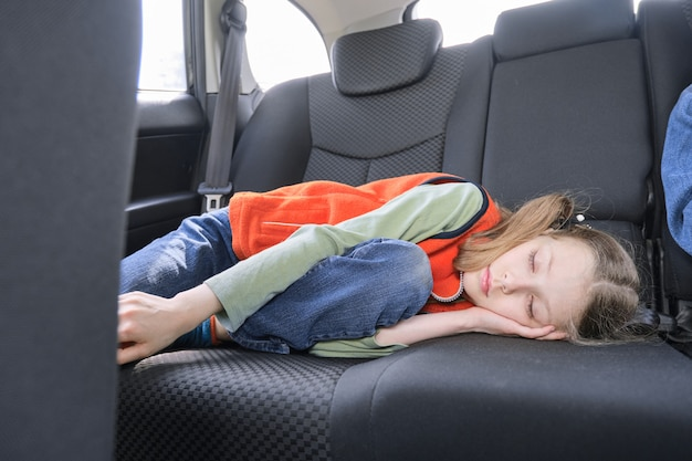 Meisjesslaap in auto, kind dat in de achterbank van voertuig ligt