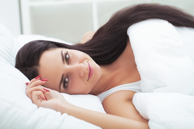Meisjesslaap laat in het weekend moe van lange werkweek rustend op pluche wit dekbed
