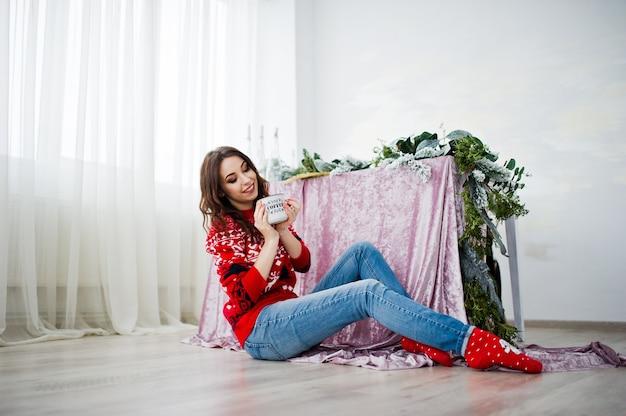 Meisjesslijtage op wintertrui zittend tegen tafel op kamer met kerstversieringen.