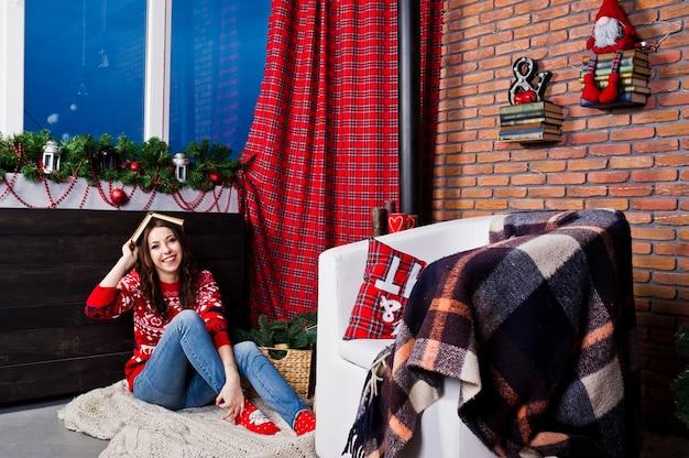 Meisjesslijtage op wintertruien op kamer met kerstversieringen.