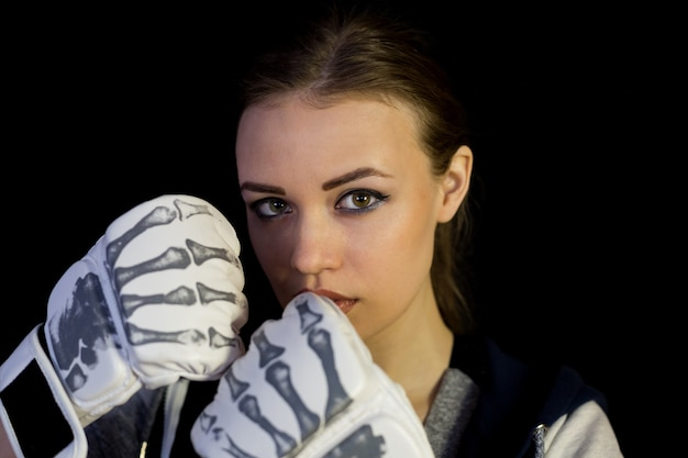 Meisjessportvrouw in handschoenen voor het in dozen doen op een zwarte achtergrond.