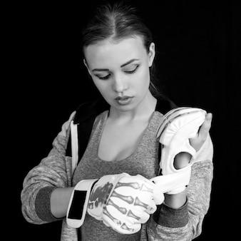 Meisjessportvrouw in handschoenen voor het in dozen doen op zwarte.