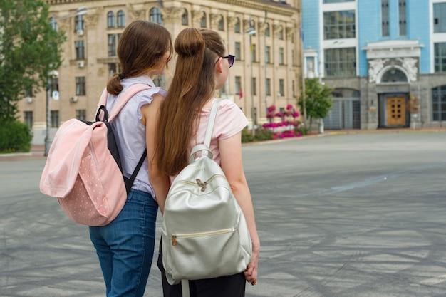 Meisjesstudent met rugzakken, achteraanzicht, wandelen in de stad