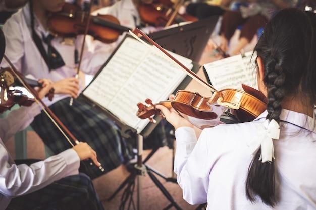Meisjesstudenten die viool in de groep spelen.