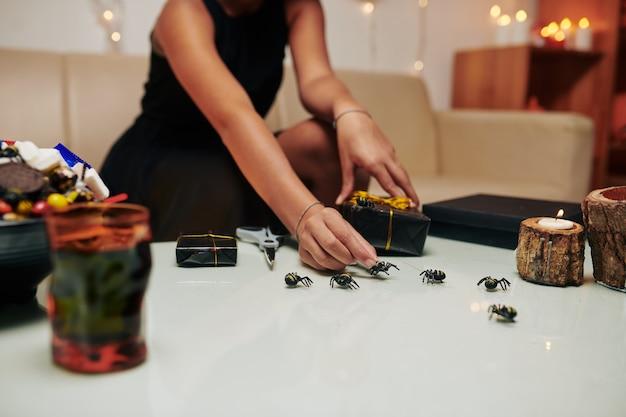 Meisjestafel met plastic spinnen, brandende kaarsen en cadeautjes verpakt in zwart papier