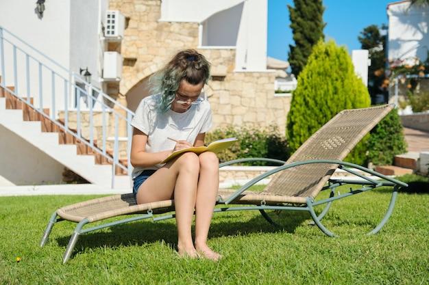 Meisjestiener die met potloodnotitieboekje bestudeert. vrouwelijke student zit in de tuinstoel in de achtertuin, zonnige zomerdag