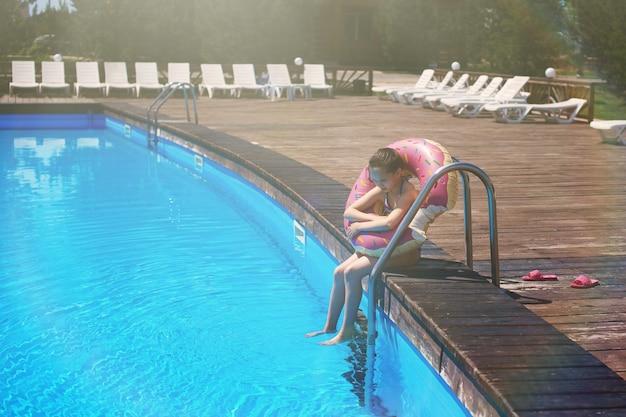 Meisjestiener in een zwempak met een opblaasbare ring zit aan de rand van het zwembad met blauw water bij de trap.