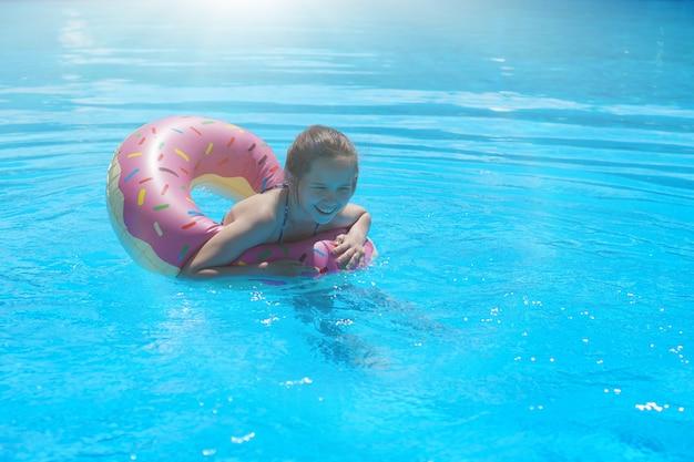 Meisjestiener in een zwempak zwemt met een opblaasbare ring in het zwembad met blauw water.