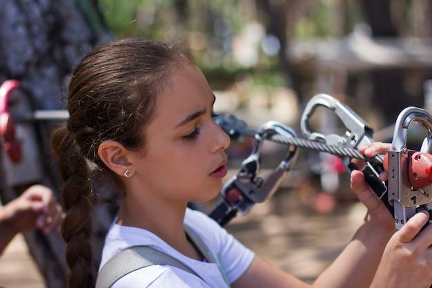 Meisjestiener met beklimmend materiaal in een kabelpretpark