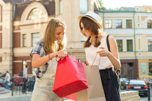 Meisjestieners in stadsstraat bekijken aankopen in boodschappentassen