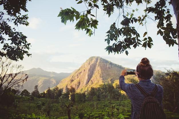 Meisjestoerist die bergen en theeplantages in sri lanka fotografeert