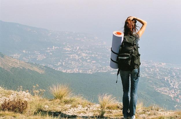 Meisjestoerist in de bergen met een rugzak op de achtergrond van de stad