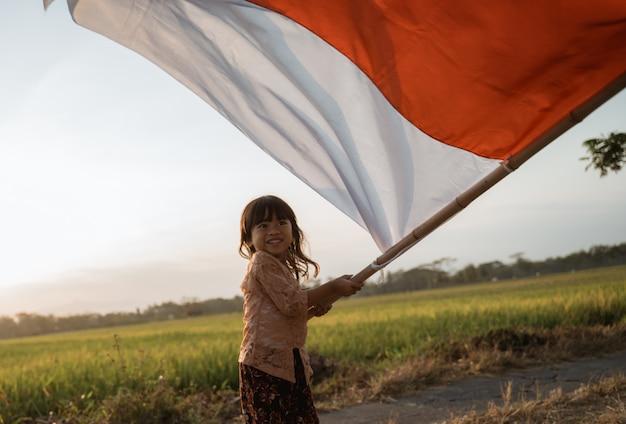 Meisjestrots die indonesische vlag met geluk klappen