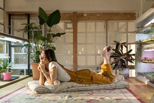Meisjestuinman die op vloer in serre of huistuinkamer met kamerplanten ligt