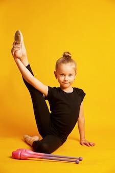 Meisjesturner leidt met gymnastiekclubs op gele achtergrond op. professionele sporten voor kinderen. mooi tienermeisje dat ritmische gymnastiekoefeningen doet