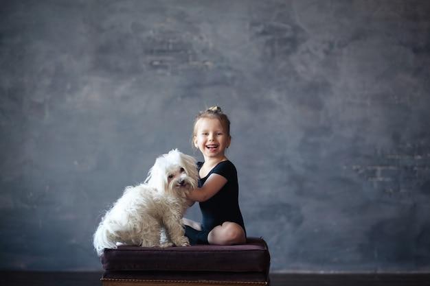 Meisjesturner zit op een stoel met haar hond en lacht