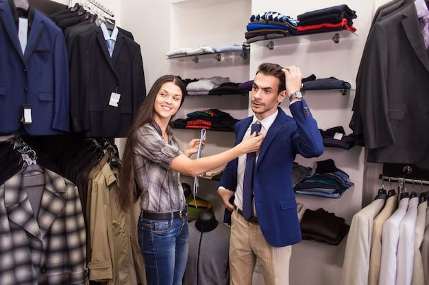 Meisjesverkoper helpt bij het ophalen van een klant in een herenmodezaak met stropdas