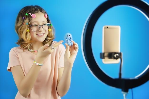 Meisjesvlogger praat online op video op smartphone over speelgoed dat met haar eigen handen is gemaakt