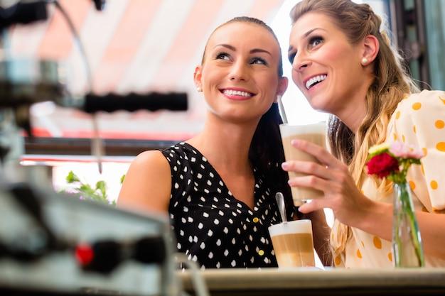 Meisjesvrienden die latte macchiato in koffiebar drinken