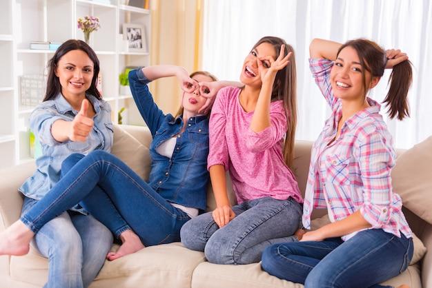 Meisjesvrienden die op de bank zitten en vooraan glimlachen.