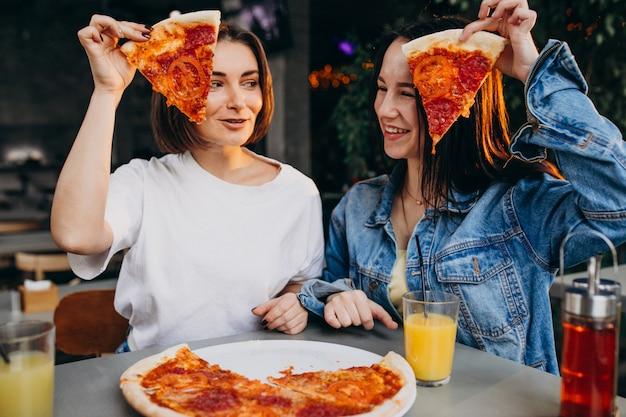 Meisjesvrienden die pizza hebben bij een bar in een lunchtijd