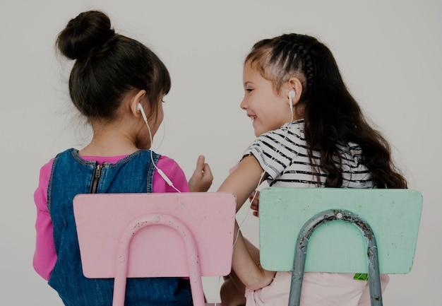 Meisjesvrienden het luisteren muziek die op witte achtergrond zitten
