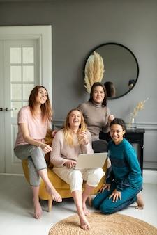 Meisjesvriendschap online het winkelen concept. vier mooie vrienden zitten thuis en bestellen via internet.