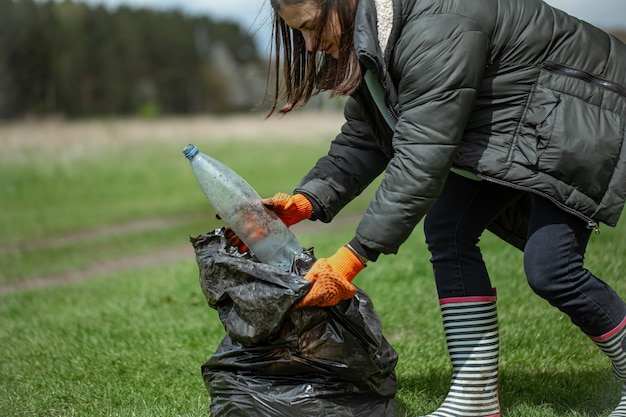 Meisjesvrijwilliger verzamelt afval in het bos, zorgt voor het milieu.