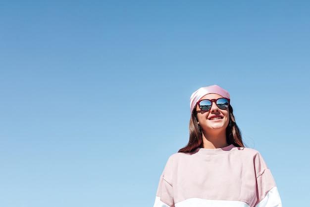 Meisjesvrouw met roze hoofddoek en zonnebril. internationale borstkankerdag, met de lucht op de achtergrond.