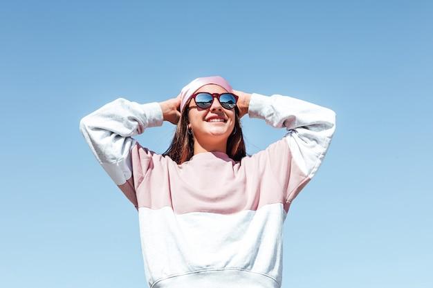 Meisjesvrouw met zonnebril, die haar pinkheadscarf bindt. internationale borstkankerdag, met de lucht op de achtergrond.
