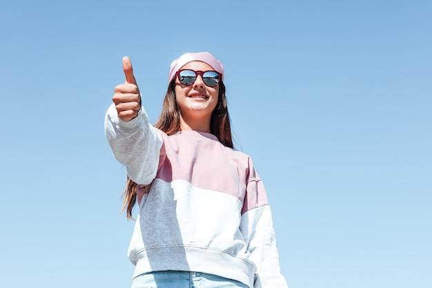 Meisjesvrouw met zonnebril en roze hoofddoek op haar hoofd, die haar duim opheft. internationale borstkankerdag, met de lucht op de achtergrond.