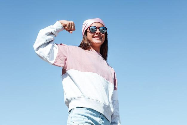 Meisjesvrouw met zonnebril en roze hoofddoek op haar hoofd, knijpt in haar arm als teken van kracht. internationale borstkankerdag, met de lucht als achtergrond.