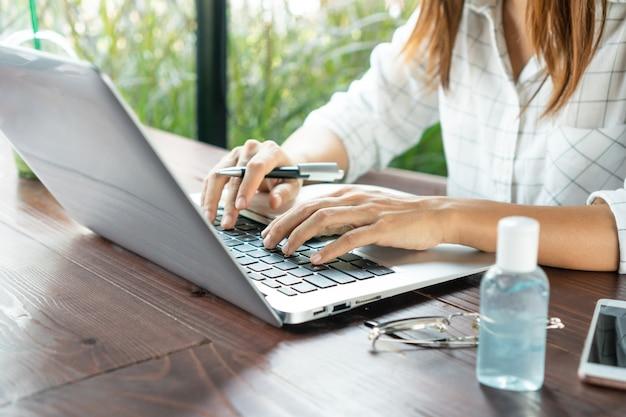 Meisjeswerk op laptop met ontsmettingsgel op bureau. beschermende maatregelen om de overdracht van covid 19 te voorkomen