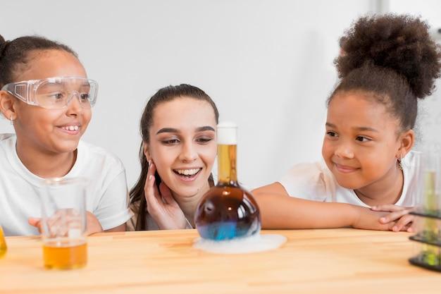 Meisjeswetenschappers en vrouw die op een chemieexperiment letten