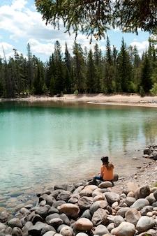 Meisjeszitting bij de oever van het meer, edith lake, jasper national park, alberta, canada