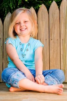 Meisjeszitting door houten omheining, het glimlachen, portret
