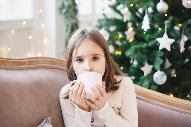 Meisjeszitting en het drinken van thee of een drank van een witte mok