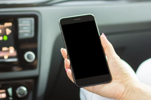 Meisjeszitting in de auto die een smartphone in haar hand, close-up houden