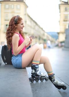 Meisjeszitting in de straat, die rolschaatsen dragen