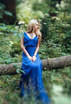 Meisjeszitting in een boom met een lange kleding