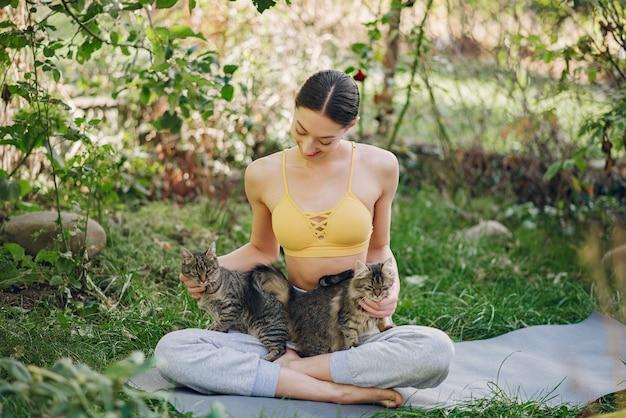 Meisjeszitting in een de zomerpark met leuke kat