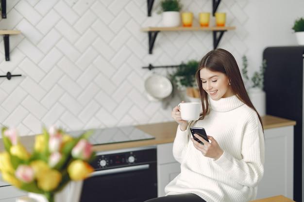 Meisjeszitting in een keuken en het drinken van een koffie