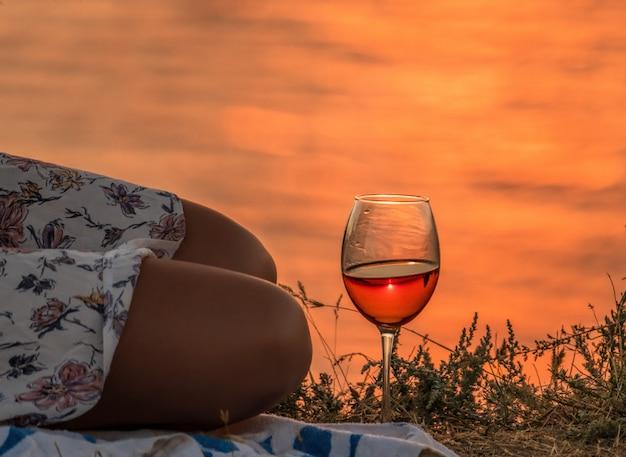 Meisjeszitting met een glas wijn bij zonsondergang