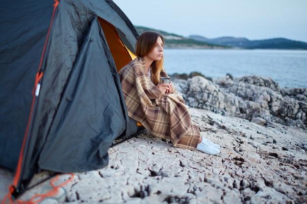 Meisjeszitting onder tenten, in plaid wordt verpakt, houdend kop van geurige thee die.