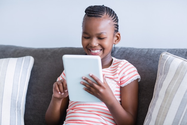 Meisjeszitting op bank die digitale tablet gebruiken