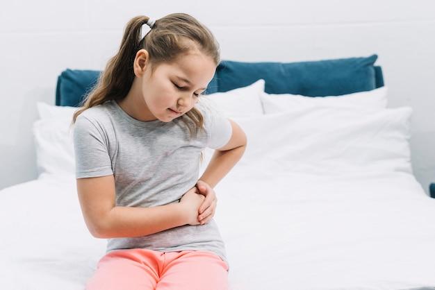 Meisjeszitting op bed die buikpijn hebben