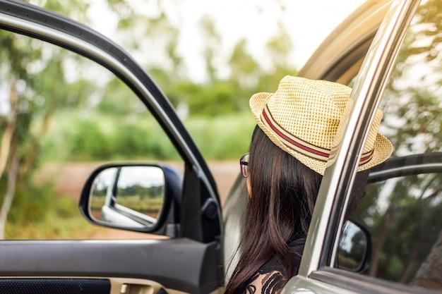 Meisjeszitting op de auto en open de deur bij de parkparkeerterrein.