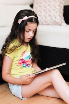 Meisjeszitting op de vloer met haar tablet